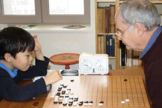 Le jeune Raphaël Caï (7 ans) et le président Jean-Paul Morère posent à tour de rôle des pierres noires et blanches sur le goban.