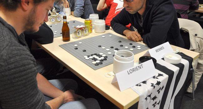 Deux adversaires posant tour à tour de rôle des «pierres» noires et blanches sur le Goban./ DDM, Th. G.